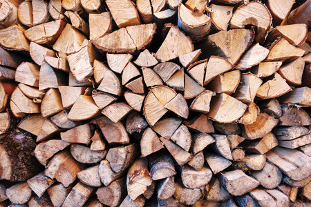 Background texture of chopped wood or logs end on in a stack for winter fuel in a full frame view