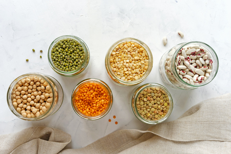 Open glass jars full of assorted dried legumes with mung beans, beans, lentils and peas over a white background in a healthy diet and nutrition concept