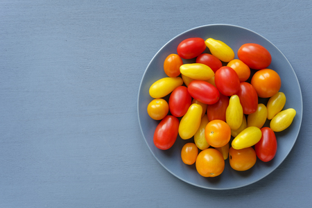 Grey plate full of small red and yellow homegrown tomatoes, viewed from above on grey background with copy space Stock Photo