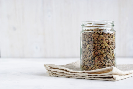Dried green lentils stored in a glass jar standing on a folded cloth over white in a health diet concept