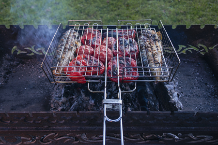 Cooking on the barbecue of Bulgarian pepper and fish, viewed in close-up from high angle