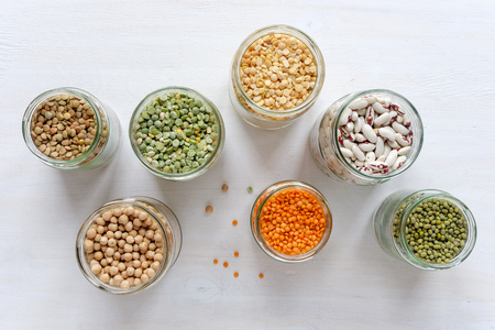 Colorful healthy dried legumes in glass jars over a textured white background with copy space viewed from overhead