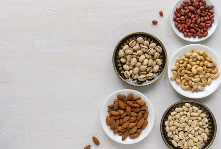 Corner border of an assorted variety of fresh nuts in individual bowls viewed from above on textured white with copy space