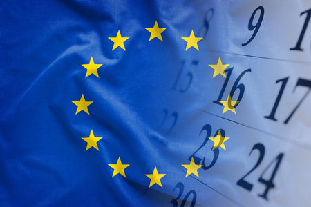 The flag of European Union with calendar of the month in the background. Full frame concept of political event date reminder