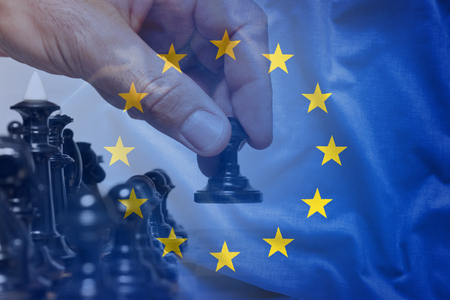European Union flag chess move concept with hand of chess player viewed behind half-transparent fabric, making a first move with black pawn