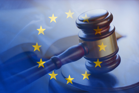 European Union flag with wooden gavel in close-up full frame background concept, symbolising legal verdict in court