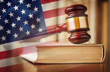 Judges gavel with law book in court and US flag in a concept of judgement, prosecution, the law and judiciary in the United States of America