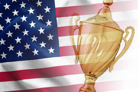 Gold trophy award superimposed on the national flag of USA in a concept of a championship win, the best, sport or competition