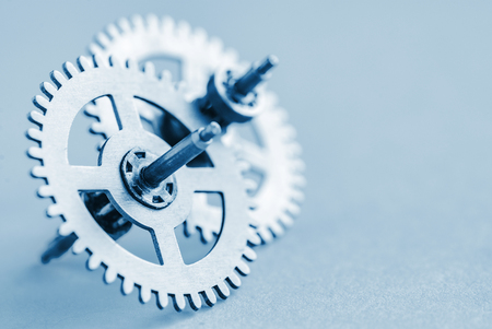 Closeup on a small steel toothed gear wheel or cog with a second behind conceptual of industry and engineering with copy space on grey