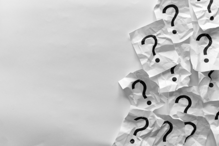 Border of crumpled question marks on cards over a white background with copy space in a conceptual image