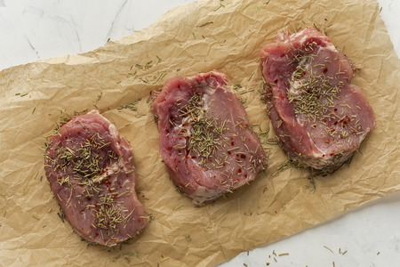 Three pieces of raw meat spiced with rosemary and placed on crumpled cooking paper. Viewed from above