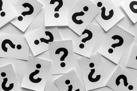 Bold black question marks on paper cards scattered randomly over a white background in a conceptual image Stock Photo
