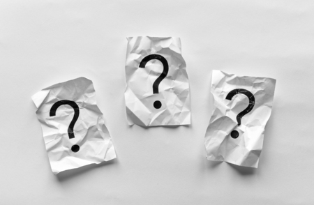 Three crumpled pages of paper with question marks on a white background in a flat lay still life Stock Photo