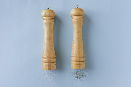 Set of wooden pepper and salt grinders or mills lying on their sides on a blue background with lateral copy space