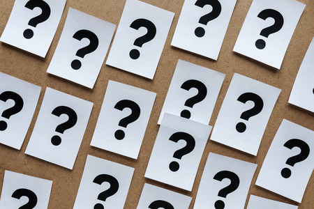Bold black question marks on paper cards scattered randomly over a wooden background in a conceptual image