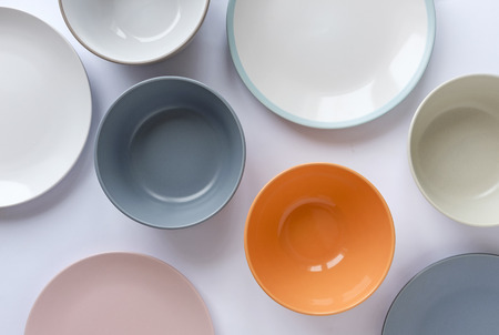 Assorted clean empty bowls and plates for food viewed from above as a full frame background on white