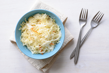 Blue bowl of shredded chopped pickled cabbage and carrot. Served with two forks on folded grey fabric towel and viewed from above on white table surface background