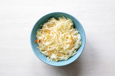 Ceramic blue bowl of fermented chopped raw cabbage and carrot, viewed from above with copy space on white background. Stock Photo