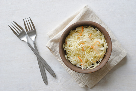 Two forks and brown ceramic bowl of chopped raw cabbage with carrot, served on folded grey towel. Viewed from above on white background