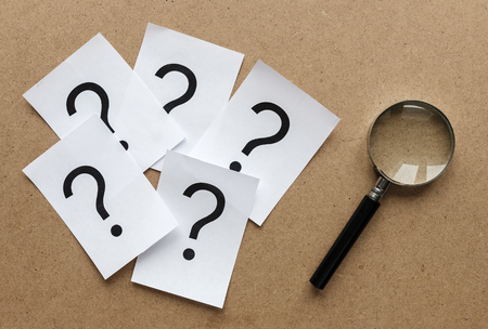 Question marks printed on white cards lying on a wooden background with a magnifying glass in a conceptual image Stock Photo