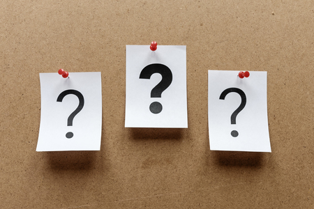 Three question marks pinned to a wooden notice board with a bold one in the centre printed on white paper cards Stock Photo