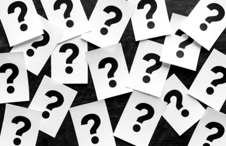 Bold black question marks on paper cards scattered randomly over a black background in a conceptual image