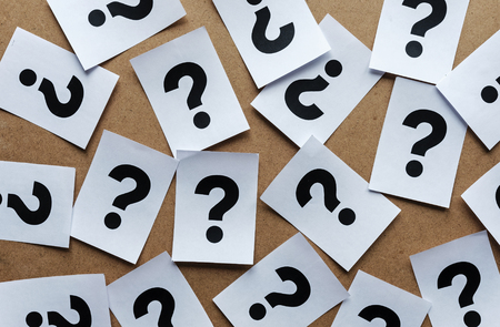 question marks on paper cards scattered randomly over a wooden background in a conceptual image
