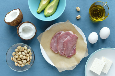 Three raw red meat steaks on cooking paper, cheese, avocado and pistachios on plates, ripe coconut and glass of olive oil viewed from above in kitchen ingredients concept layout