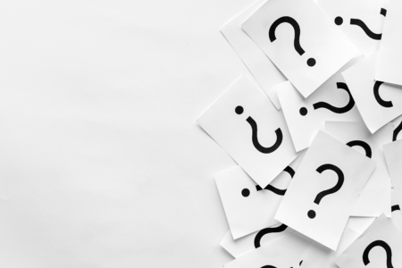 Pile of question marks printed on white cards forming a side border over a white background with copy space in a conceptual image
