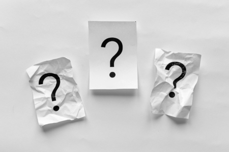 Three question marks on white paper with two crumpled up flanking one in the centre in a conceptual image with copy space