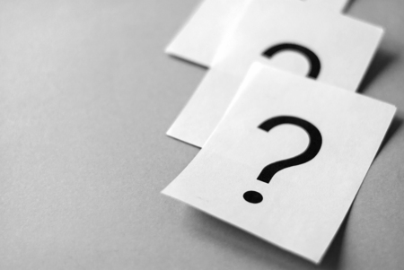 White cards with printed question marks on grey background with copy space. Queue of questions to be answer concept Stock Photo
