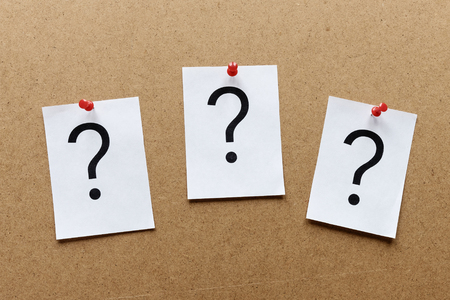 Three question marks pinned in a row with colorful red thumb tacks on a wooden notice board with copy space in a conceptual image Stock Photo