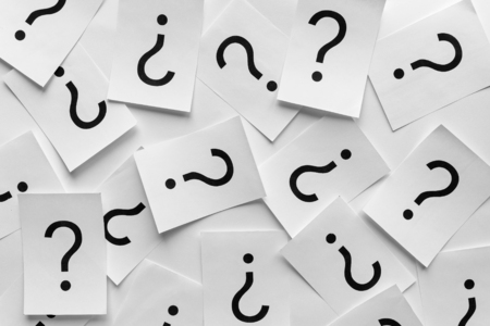 Background texture of printed question marks on white sheets of paper scattered randomly overlapping in a full frame view