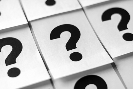 Black question marks printed on white sheets of paper arranged in full frame background concept