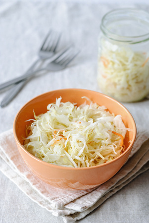 Orange bowl with crunchy sauerkraut served on napkin with forks on table Stock Photo