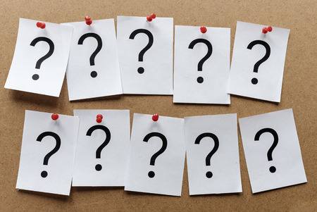 Two rows of question marks printed on individual white cards pinned to a wooden notice board with thumb tacks