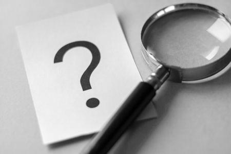 Black question mark printed on white paper card on the table next to magnifying glass, viewed in close-up. Search and questioning concept