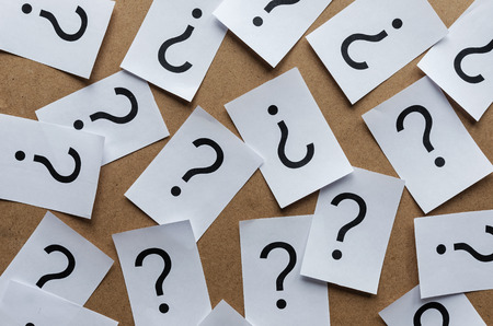 black question marks on paper cards scattered randomly over a wooden background Stock Photo