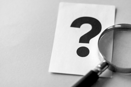 Question mark printed on white sheet of paper and magnifying glass on the table. Search for answers concept with copy space on grey background