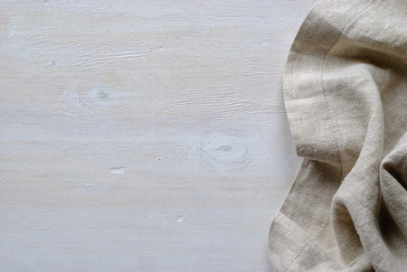 Folded and gathered linen fabric side border in a neutral weave over textured white painted wood with copy space Stock Photo