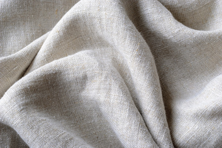 Gathered and folded texture of woven linen fabric with natural fibres in a close up full frame view