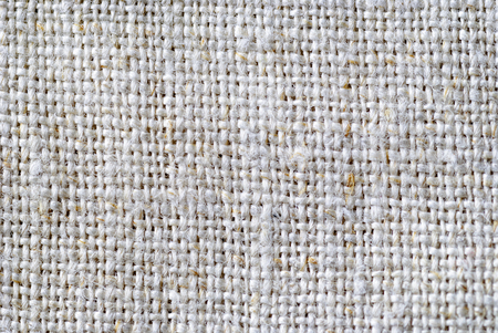 Close up on the weave of natural linen fabric in a neutral color in a full frame background texture