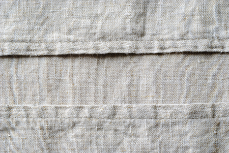 Woven linen fabric showing the stitching on the seams arranged neatly in parallel lines in a close up full frame view