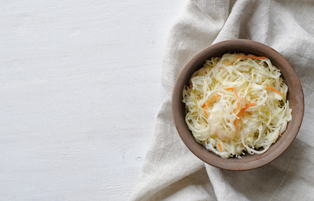 Top view of brown ceramic bowl of sauerkraut with chopped cabbage and carrot on grey towel sitting on white table surface Stock Photo