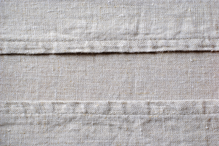 Stitched seams or edges on natural linen textile arranged as two borders to the sides over woven fabric centre with copy space