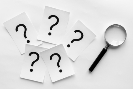 Question marks printed on white cards lying on a white background with a magnifying glass in a conceptual image