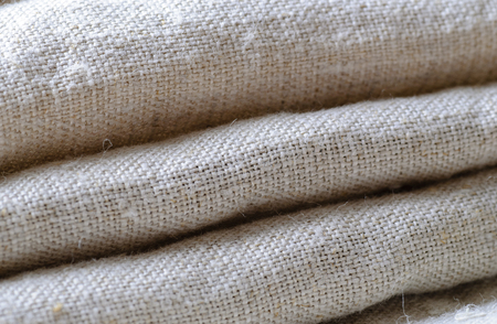 Neatly stacked folded linen material viewed at an oblique angle in a full frame view showing the detail of the weave Stock Photo