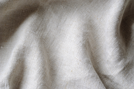 Soft folds of a natural woven linen fabric in close up detail in a full frame background texture Stock Photo