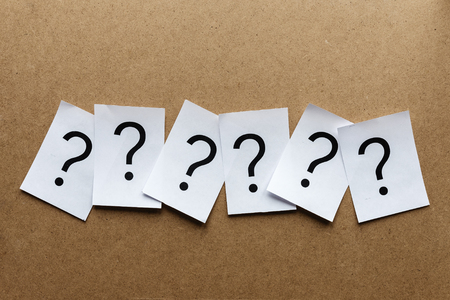 Line of question marks on pages of clean white paper over a wooden background with copy space above and below Stock Photo