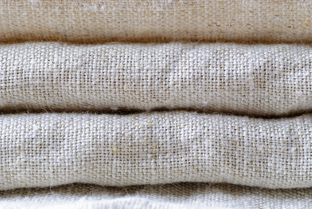 Neatly folded woven linen fabric in a neutral shade stacked on top of one another in a close up full frame background
